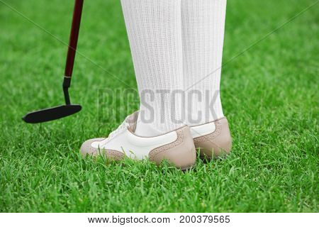 Legs of young golf player on course in summer day