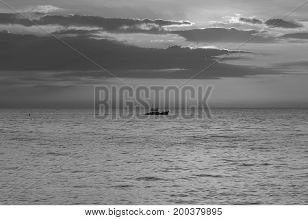 Black and White Alone fishing boat on big ocean abstract background
