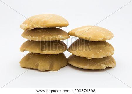 Stack of hard palm sugar on white background