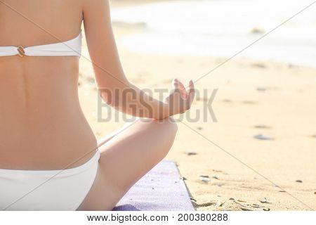 Beautiful young woman practicing yoga on sea beach