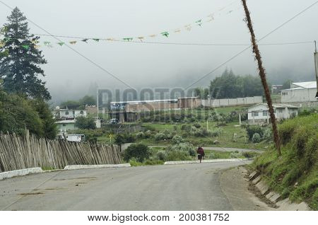 EL CONEJO. PEROTE, VERACRUZ, MEXICO- JULY 8, 2017: Rural landscape. A woman walks during a foggy day at El Conejo, a town near El Cofre de Perote.