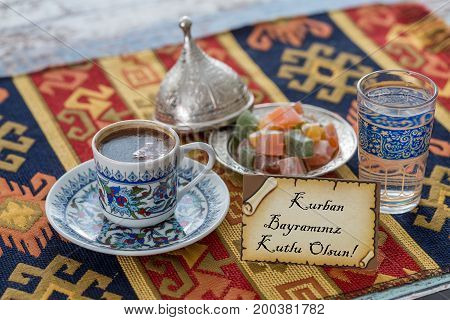Happy eid al adna text in turkish on greeting card with turkish coffee delights on traditional tablecloth poster
