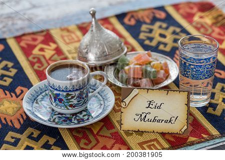 Eid mubarak text on greeting card with turkish coffee delights on traditional tablecloth poster