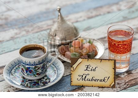 Eid mubarak text on greeting card with turkish coffee delights on vintage table poster