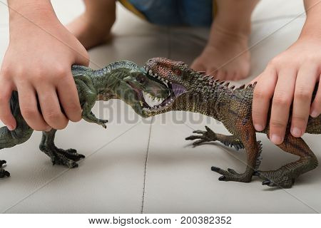 kid playing with Carcharodontosaurus and tyrannosaurus toys fighting each other