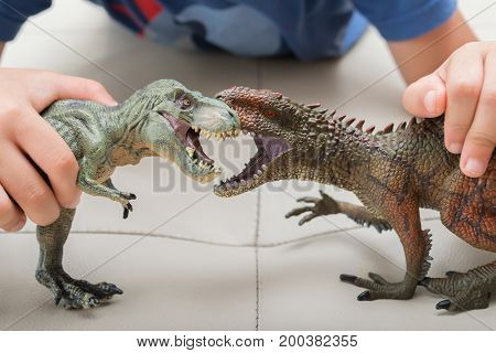 kid playing with Carcharodontosaurus and tyrannosaurus toys fighting each otherkid playing with Carcharodontosaurus and tyrannosaurus toys fighting each other