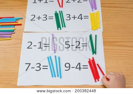 kid learning simple subtraction and addition by counting numbers of sticks
