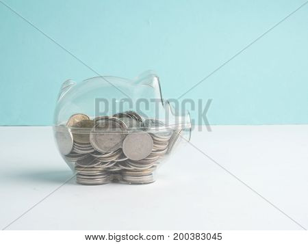 transparent see through piggy bank filled with coins on wood background.Saving investment colorful concept.Hand putting coin into pink piggy bank.Hand putting coin into pink piggy bank