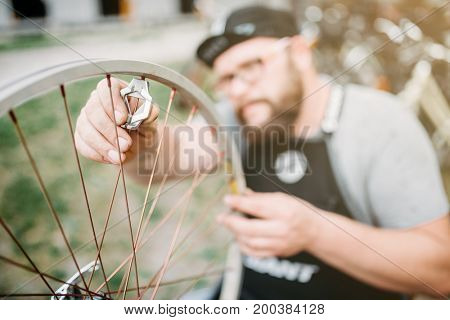 Bicycle master in apron adjusts bike spokes