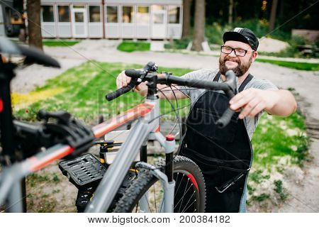 Mechanic adjusts the bicycle handlebars and brakes