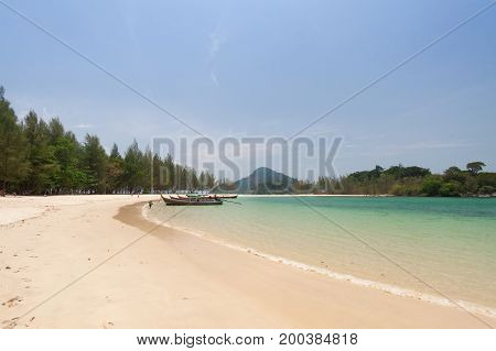 Tropical white sand beach with traditional thai longtail boat .