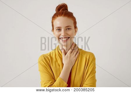 Headshot Of Cute Redhead Girl With Hair Bun Wearing Yellow Cardigan Looking At Camera With Shy Charm