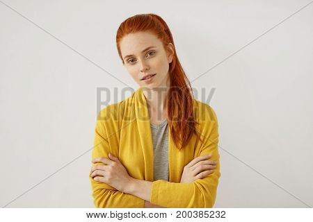 Portrait Of Female Model With Ginger Pony Tail, Freckled Face, Green Shining Eyes, Keeping Her Hands