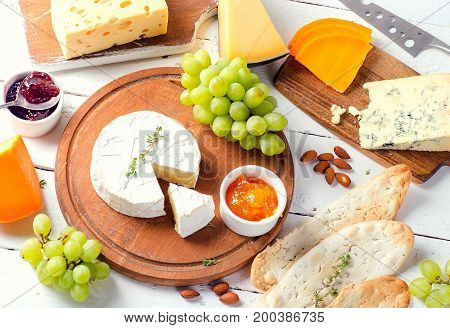 Different Kinds Of Cheeses  With Grapes And Jam On White Wooden Table