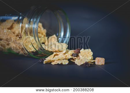 whole grain cereal flakes which mixed berry fruit and raisins. Cereal cornflakes for breakfast on black background