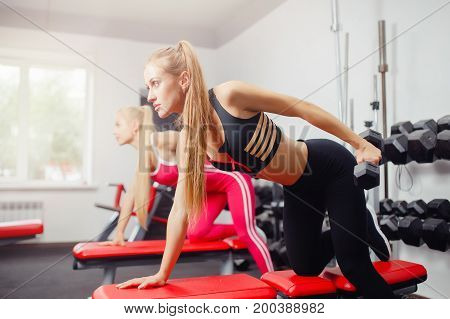 girls are arranged in a row, lift dumbbell by hand, look forward, concept is occupied by group by fitness. copyspace