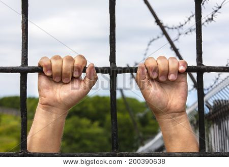 hands of a man behind bars close up background