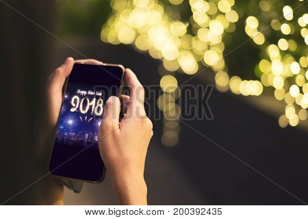 Woman Hand holding mobile with Happy new year 2018 fireworks over cityscape on screen with light bokeh backgroundDigital greeting card holiday.