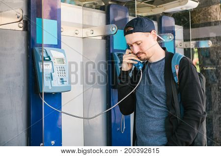 Young attractive modern man talking on the payphone, communication concept.
