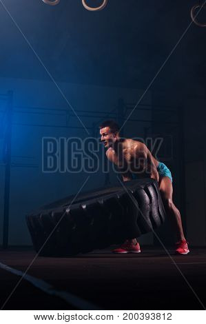 Muscular fitness man with naked torso working out with tire in gym. Weightlifting or functional training. Sports and fitness concept.