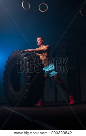Athletic young man with naked torso working out with tire in gym. Functional or weightlifting training. Sports and fitness concept.