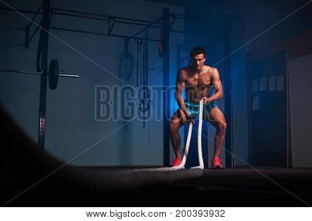 Strong fitness model working out with battle ropes at gym. Functional training. Sports and fitness concept.
