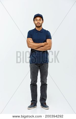 Delivery Concept - Handsome African American delivery man crossed arms over isolated on Grey studio Background. Copy Space.