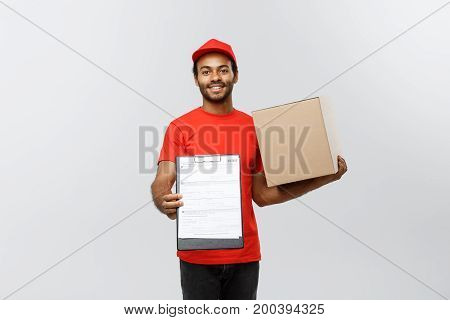 Delivery Concept - Portrait of Handsome African American delivery man or courier showing a confirmation document form to sign. Isolated on Grey studio Background. Copy Space.