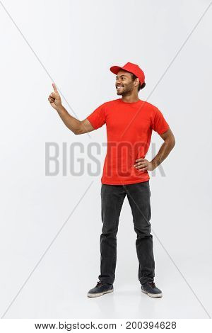 Delivery Concept - Portrait of Happy African American delivery man pointing hand to present something. Isolated on Grey studio Background. Copy Space.