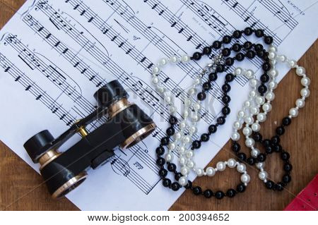 Black Binoculars And Necklace On Music Notes Sheet. Trip To The Theater. Top View.