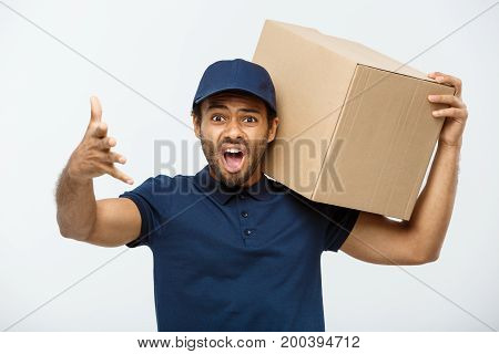 Delivery Concept - Portrait of Serious African American delivery man showing silly aggressive expression with holding a box package. Isolated on Grey studio Background. Copy Space.