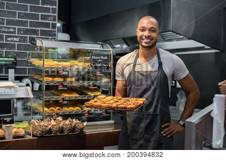 Smiling black baker with apron holding tray of small pastry and looking at camera. Young african chef holding sweet tray at cafeteria. Happy black man smiling at bakery.