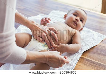 Mother hands changing baby nappy. Mother putting diaper on her hispanic son lying in nursery. Close up of mother giving baby diaper change at home.
