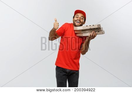 Delivery Concept - Portrait of Handsome African American Pizza delivery man showing thump up. Isolated on Grey studio Background. Copy Space.