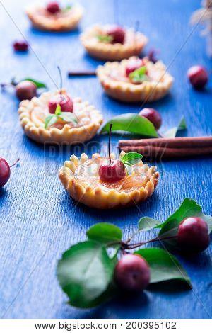 Apple Caramel Little Tarts On Blue Rustic Background. French Tatin With Paradise Apple