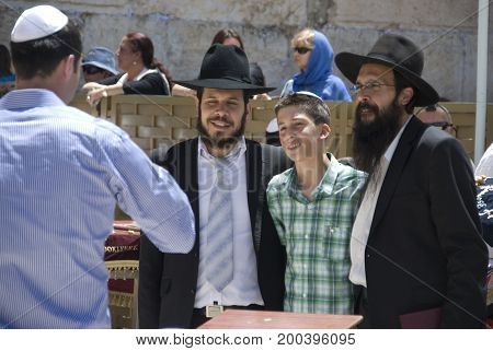 'Jerusalem, Israel - May 07, 2012: Orthodox jews with black hats and jews with kippa on square in front of the Western Wall in Jerusalem, in May 2012'