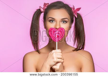 beautiful young woman with pink makeup and two girly ponytails holding red heart shape lollypop. beauty shot on pink background. copy space.