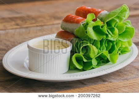 Fresh spring rolls with fresh vegetable and crab stick served with spicy salad cream dipping sauce. Rolls salad or fresh spring roll on white plate healthy delicious food for appetizer or meal. Delicious fusion food: fresh spring rolls.