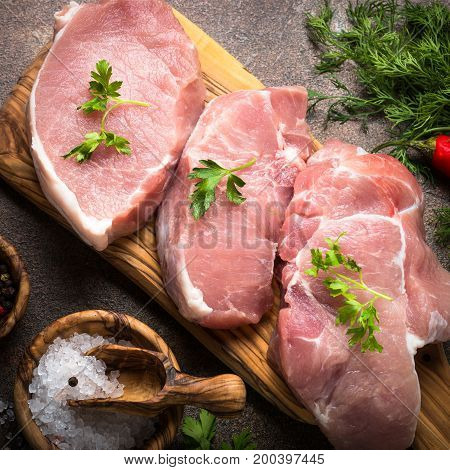 Raw meat. Fresh pork steak on a cutting board with herbs and spices. Square.