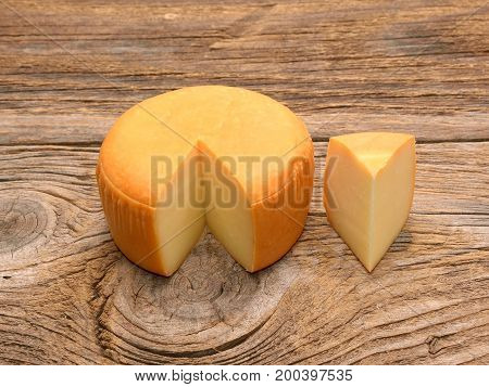 Cheese wheel isolated on wood Organic food