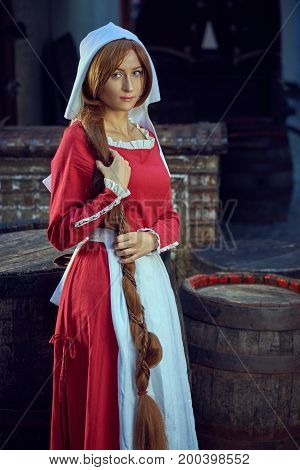 Townswoman in red dress with an apron and chaperone on the street. Costume stylized of later Middle Ages on 15/ 16th century.