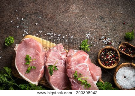 Raw meat. Fresh pork steak on a cutting board with herbs and spices on dark stone table. Top view.