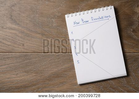 new year resolutions tempate with notepad on wood table, copy space for text