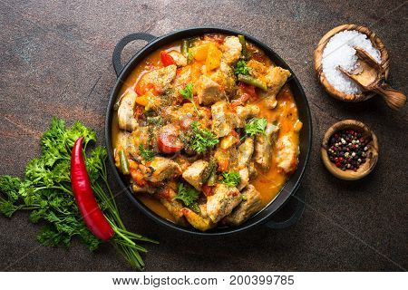 Stewed pork with vegetables in tomato sauce in a cast-iron pan. Top view on dark stone background.