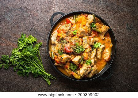 Stewed pork with vegetables in tomato sauce in a cast-iron pan. Top view on dark background.