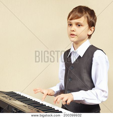 Young beginner pianist play the keys of the synthesizer