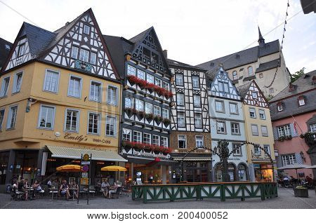 Cochem, Germany - August 2012: Main square with half-timbered houses and people in cafes in Cochem in August 2012