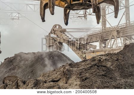 Industrial loading equipment. Hot slag in the outdoors shop of metallurgy. Heavy industrial metallurgical foggy landscape.