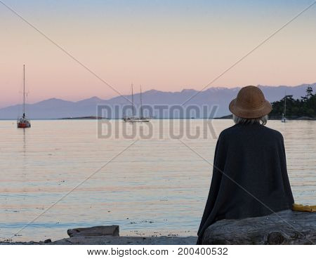 A gray haired woman watching the sailboats in the bay during sunset. She is seated on driftwood with her back to the camera.
