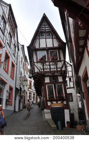 Bernkastel-Kues, Germany - August 2012: Thin half-timbered house, Bernkastel-Kues, Germany, with people on the alleys, in August 2012